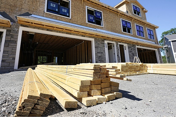 In this June 24, 2021 photo, lumber is piled at a housing construction site in Middleton, Mass. Rising costs and shortages of building materials and labor are rippling across the homebuilding industry, which accounted for nearly 12% of all U.S. home sales in July. Construction delays are common, prompting many builders to pump the brakes on the number of new homes they put up for sale. As building a new home gets more expensive, some of those costs are passed along to buyers. ( Elise Amendola/AP)