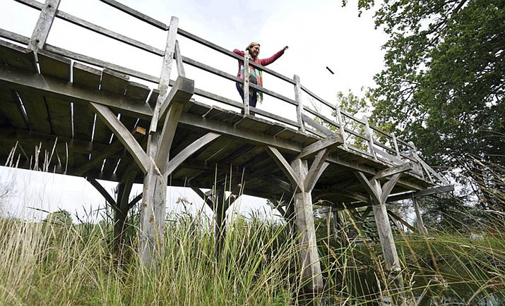 """Silke Lohmann of Summers Place Auctions stands on the original Poohsticks Bridge from Ashdown Forest, featured in A.A. Milne's Winnie the Pooh books and E.H. Shepard's illustrations, near its original location in Tonbridge, Kent, England, Thursday, Sept. 30, 2021. The adventures of the honey-loving bear """"Winnie the Pooh"""" have captivated children and their parents for nigh on 100 years. Fans now have a chance to own a central piece of Pooh's history, when a countryside bridge from the south of England goes up for auction this week. (Gareth Fuller/PA via AP)"""