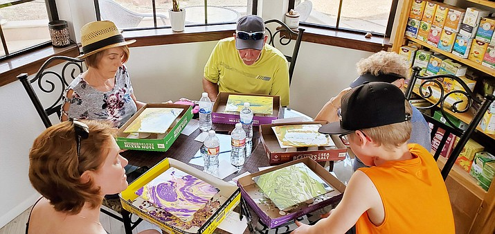 A group of clients work on their paint pouring projects. (Penny Pennell/Courtesy)