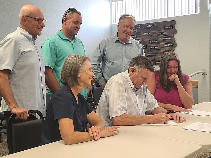 Stanley Bullard, the president of the Verde Water System signs the document Thursday, Sept. 30, 2021, selling the water system to the town. In the photo in back from left to right is former Camp Verde Mayor Tony Gioia, Justin Bullard and Town Manager Russ Martin. In front from left to right is current Mayor Dee Jenkins, Stan Bullard, and Stacy Bullard. (Vyto Starinskas/Independent)