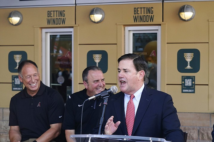 Gov. Doug Ducey, right, speaks at a news conference Thursday, Sept. 9, 2021, in Phoenix. A key federal official is telling Ducey he cannot use COVID grant dollars to penalize schools that impose mask mandates. And if Ducey doesn't fix the problem he is threatening to take back the money. (Ross D. Franklin/AP, file)