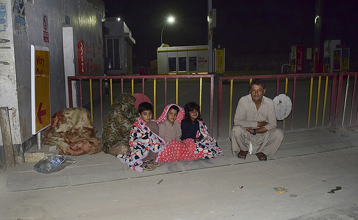 A family gather outside their house following a severe earthquake hit the area, in Quetta, Pakistan, Thursday, Pakistan. A powerful earthquake shook parts of southwestern Pakistan early Thursday.(Arshad Butt/AP)