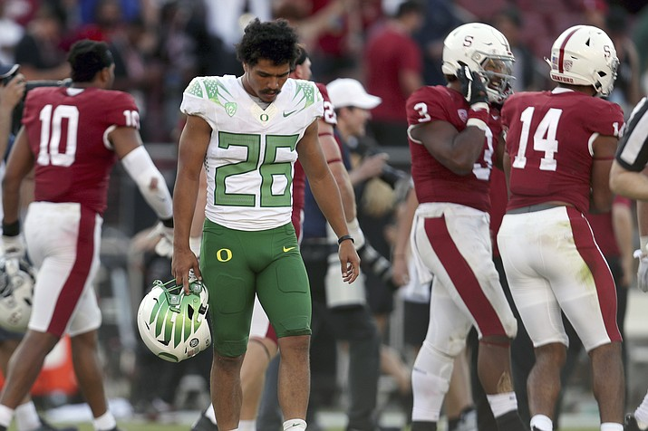 Oregons' Travis Dye (26) walks off the field after losing to Stanford after overtime in an NCAA game in Stanford, Calif., Saturday, Oct. 2, 2021. (Jed Jacobsohn/AP)