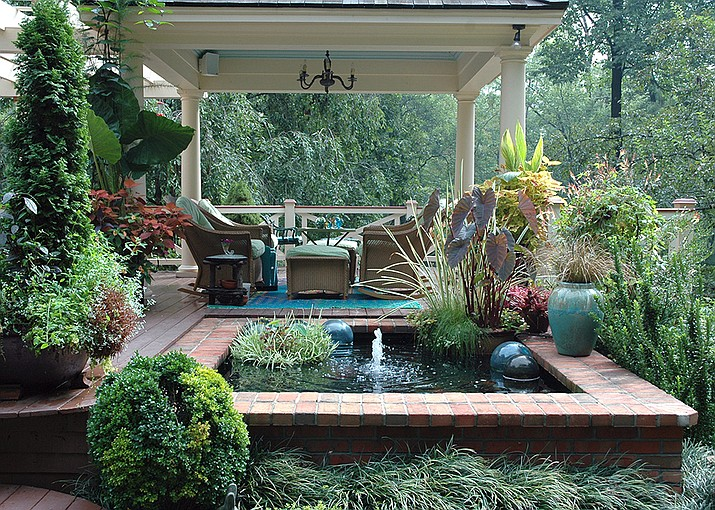 For a tropical escape include leafy plants like elephant ears and banana plants in pots, wicker furniture, a water feature and colorful flowers like hibiscus and mandevilla. (Melinda Myers.com/Courtesy