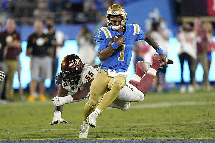 UCLA quarterback Dorian Thompson-Robinson, right, avoids a tackle by Arizona State defensive lineman Omarr Norman-Lott as he runs the ball during the second half of an NCAA college football game Saturday, Oct. 2, 2021, in Pasadena, Calif. Arizona State won 42-23. (Mark J. Terrill/AP)