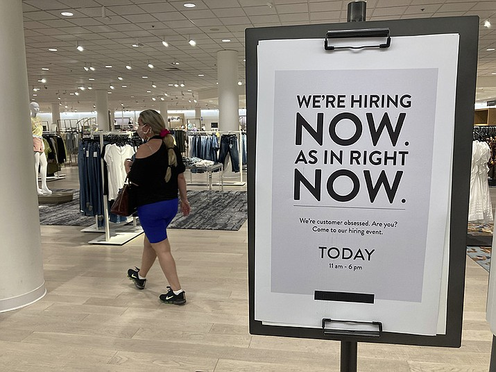 A customer walks behind a sign at a Nordstrom store seeking employees in Coral Gables, Fla. On Friday, Oct. 8, U.S. employers added just 194,000 jobs in September, a second straight tepid gain and evidence that the pandemic still has a grip on the economy with many companies struggling to fill millions of open jobs. (Marta Lavandier, AP File)