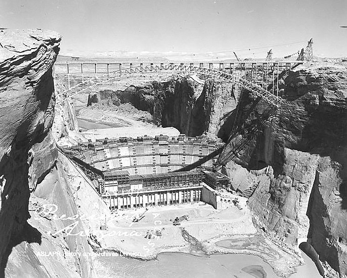 In 1956, construction began on Glen Canyon Dam, a structure 573 feet (175 meters) above the bed of the Colorado River, 1,500 feet (457 meters) long at the crest and containing a lake of over 28 million acre feet of water extending 186 miles (299 Km) behind the dam. (Arizona State Library, Archives & Records/Courtesy)