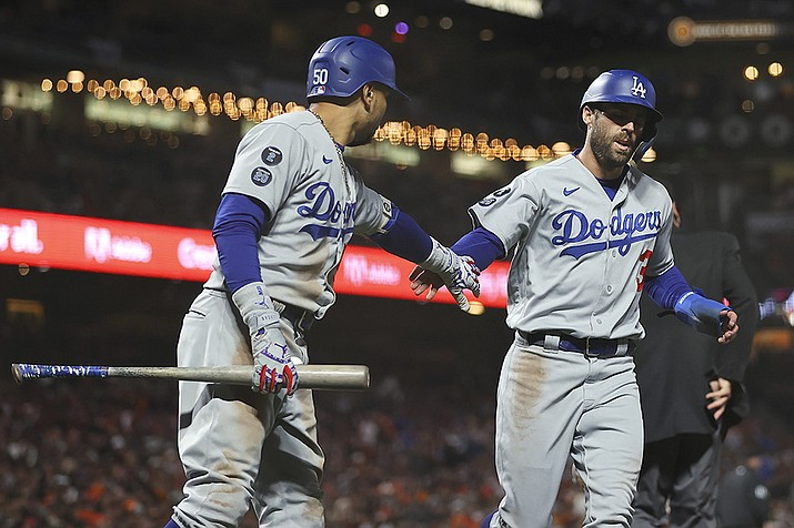 Los Angeles Dodgers' Chris Taylor, right, is congratulated by Mookie Betts after scoring against the San Francisco Giants during the eighth inning of Game 2 of a baseball National League Division Series Saturday, Oct. 9, 2021, in San Francisco. (John Hefti/AP)