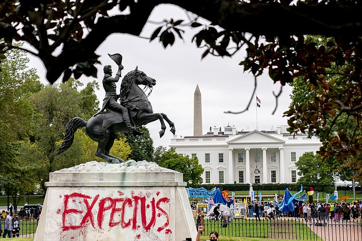 """The words """"Expect Us"""" are spray painted on the base of the Andrew Jackson statue in Lafayette Park as Indigenous and environmental activists protest in front of the White House in Washington, Monday, Oct. 11, 2021. The words are part of the phrase """"Respect Us, or Expect Us"""" which indigenous women have been using while protesting oil company Enbridge's Line 3 pipeline through Minnesota. President Joe Biden on Friday issued the first-ever presidential proclamation of Indigenous Peoples Day, lending the most significant boost yet to efforts to refocus the federal holiday celebrating Christopher Columbus toward an appreciation of Native peoples. (Andrew Harnik/AP)"""