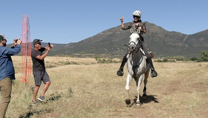 Susan Kramer OF Peoria crosses the finish line on her horse after finishing the 50-mile course, beating the first runner by 3 minutes after the deduction for safety checks, at the Man vs. Horse Race on Saturday, Oct. 9, 2021. (Jesse Bertel/Courier)