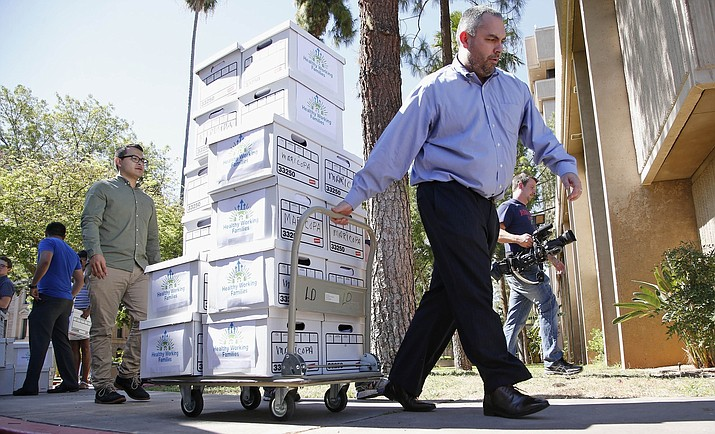 This 2016 file photo shows a state worker brings boxes to the elections office at the Arizona Capitol in Phoenix. The boxes contained more than 270,000 signatures from a group that pushed for $12 an hour minimum wage by 2020. A judge ruled Monday, Oct. 11, 2021, that the state can't take more than $1.1 million from Flagstaff as a financial penalty for the city having its own minimum wage, at least not now. (Ross D. Franklin/AP, file)