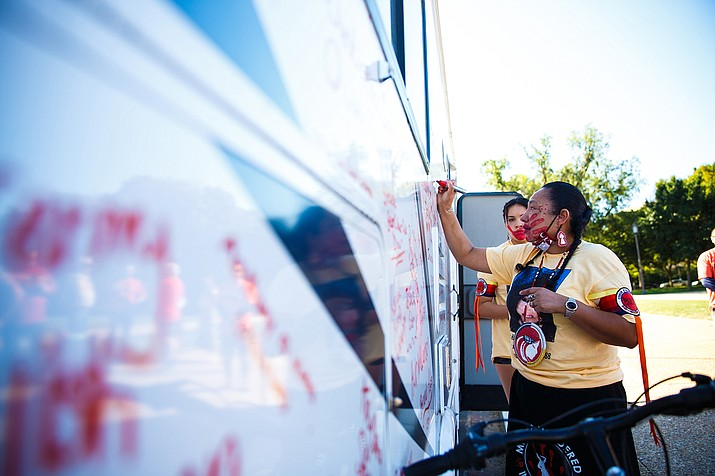 LoVina Louie, the wife of MMIW Bike Run USA organizer Duane Garvais-Lawrence, adds names to the side of the motor home that carried them on the trip. One goal of the trip was to raise $186,090 — representing what they say is the amount of women and children missing — to support MMIW help centers and families they met along the way. (Photo by Diannie Chavez/Cronkite News)