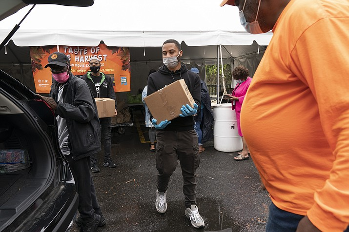Volunteer Markel Lucas, center, takes a box of food to a patron of the food bank's car, at the Town Hall Education Arts & Recreation Campus (THEARC), Wednesday, Oct. 6, 2021, in Washington. (Jacquelyn Martin/AP)