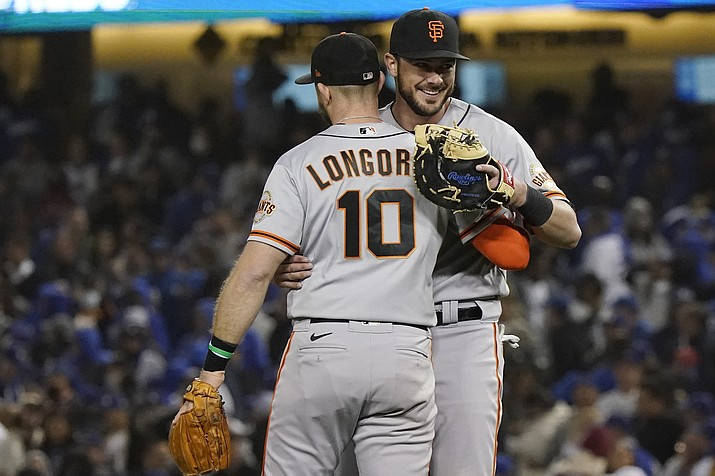 San Francisco Giants' Evan Longoria (10) hugs teammate Kris Bryant, right, after Longoria's solo home run gave the the Giants a 1-0 win over the Los Angeles Dodgers in Game 3 of a National League Division Series, Monday, Oct. 11, 2021, in Los Angeles. (Marcio Sanchez/AP)