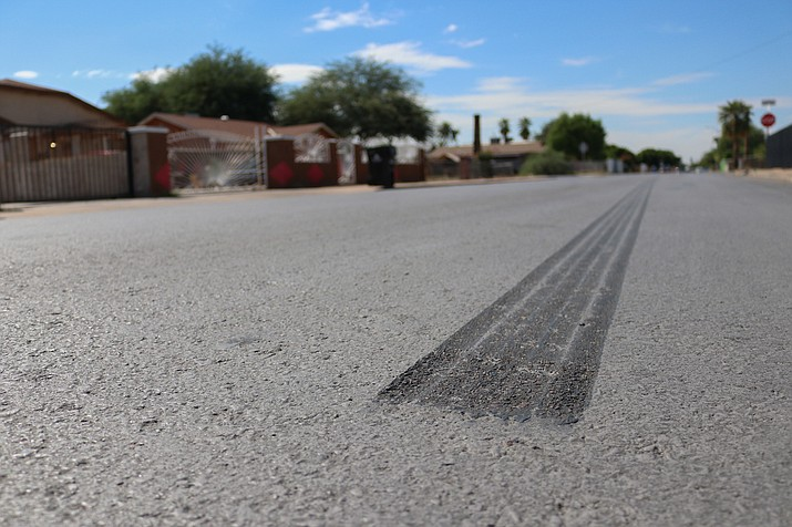 The light gray asphalt sealant is meant to reflect sunlight away from roads to reduce heat, but tire marks like this are one of the aesthetic drawbacks. (Mingson Lau/Cronkite News)