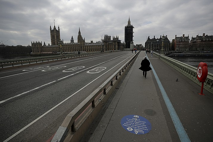 In this Tuesday, March 23, 2021 file photo, people pass over a quiet Westminster Bridge, backdropped by the scaffolded Houses of Parliament and the Elizabeth Tower, known as Big Ben, in London, during England's third coronavirus lockdown. The British government waited too long to impose a lockdown in the early days of the COVID-19 pandemic, missing a chance to contain the disease and leading to thousands of unnecessary deaths, lawmakers concluded Tuesday, Oct. 12, 2021 in a hard-hitting report. (Matt Dunham, AP File)