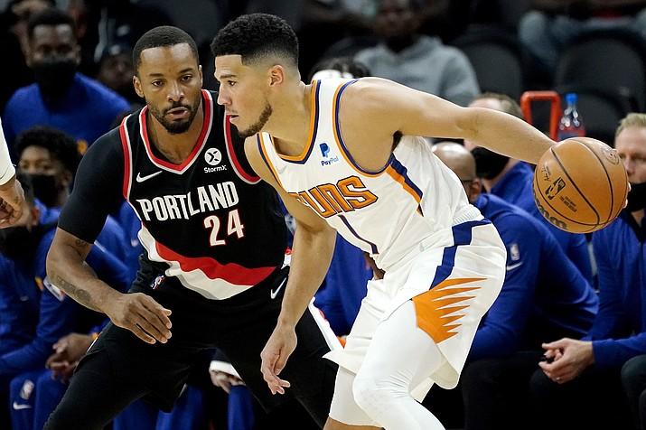 Phoenix Suns guard Devin Booker (1) looks to pass as Portland Trail Blazers forward Norman Powell (24) defends during the first half of a preseason NBA basketball game, Wednesday, Oct. 13, 2021, in Phoenix. (Matt York/AP)