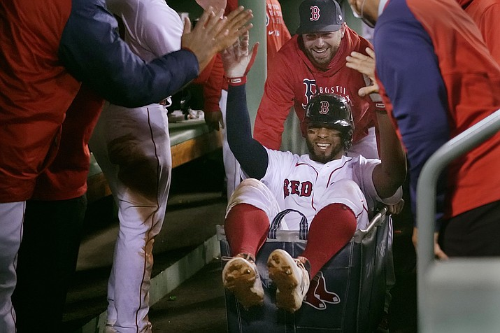 In this May 4, 2021 photo, Boston Red Sox's Xander Bogaerts high-fives teammates while being pushed in a laundry cart through the dugout after his two-run home run against the Detroit Tigers during the second inning of a baseball game at Fenway Park in Boston. Started on a lark in a last-place season, the Red Sox have continued the celebration this year and ridden it all the way to a playoff berth, a win over the rival New York Yankees in the AL wild-card game and then a four-game victory over Tampa Bay in the Division Series. (Charles Krupa/AP, File)