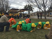 Basic wildland firefighting students practice deploying fire shelters during the 2018 Arizona Wildfire and Incident Management Academy at Embry-Riddle Aeronautical University campus in Prescott on Tuesday, March 13.